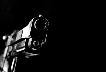 automatic handgun on black background
