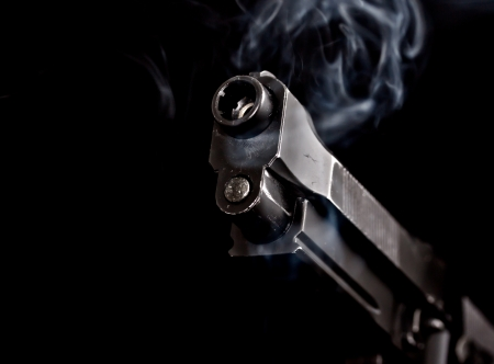 murder: handgun with gun smoke on black background