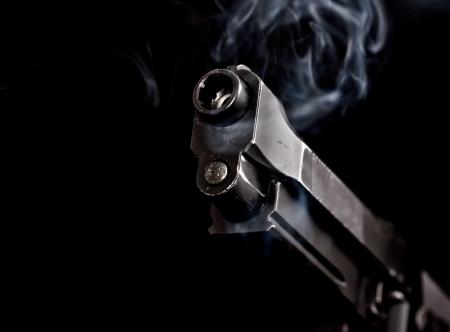 handgun with gun smoke on black background