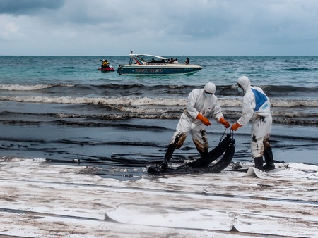 water pollution: oil spilled beach operation in Rayong, Thailand on July 31, 2013