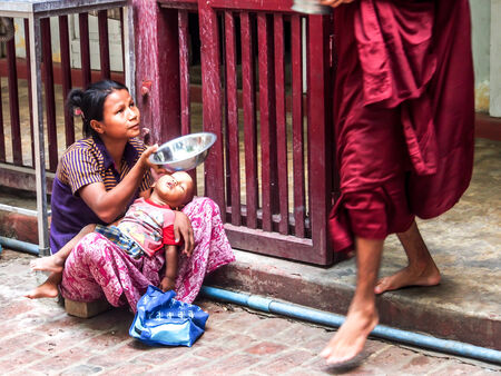 monks: beggar beg for the food from a monk in Mandalay, Myanmar