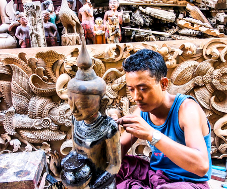 trinchante: trabajo tallador de madera en una tienda de recuerdos en Mandalay, Myanmar Editorial