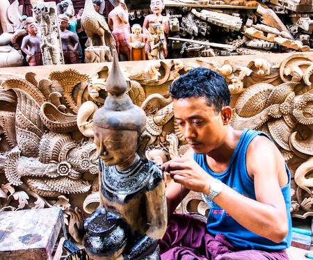 carver: wood carver work in a souvenir shop in Mandalay, Myanmar