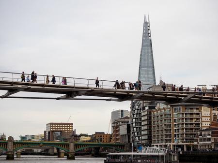 millennium: people cross Millennium bridge in London, UK