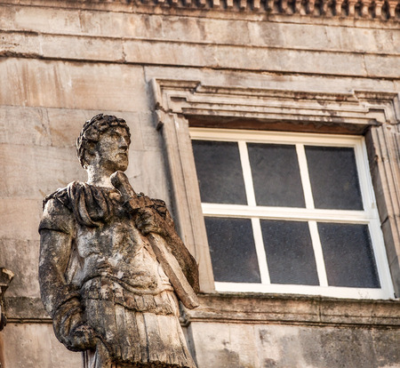 somerset: old Roman sculpture at Roman Bath historical site, Somerset, UK