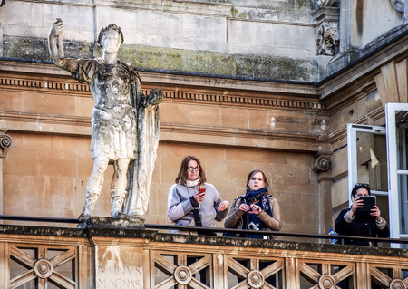 somerset: tourists with the old Roman sculpture at Bath, Somerset, UK