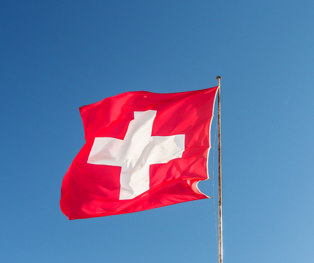 swiss culture: Swiss flag with blue sky