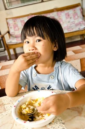 meisje eten: Kleine Aziatische meisje eet haar lunch Stockfoto