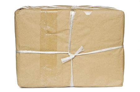 Ein Paket in braunem Papier gewickelt und mit groben Zwirn und leeres Etikett, isoliert auf weißem Hintergrund Lizenzfreie Bilder