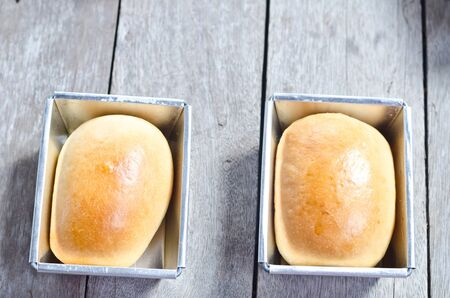 Fresh breads baked in tray on wood table photo
