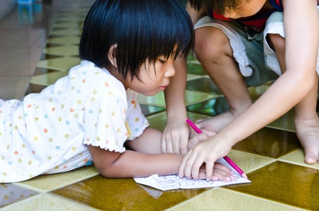 Asia girl  drawing paper on the floor with brother photo