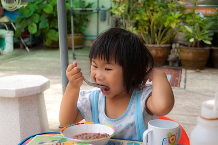 A little girl have breakfast outdoor photo
