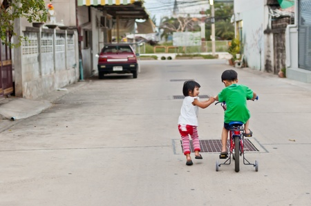 Brother and sister have fun with bicycle, love, relation ship, take care concept Stock Photo