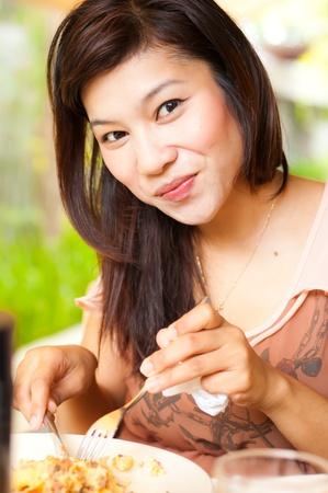 Young girl enjoying her food, look at camera Stock Photo