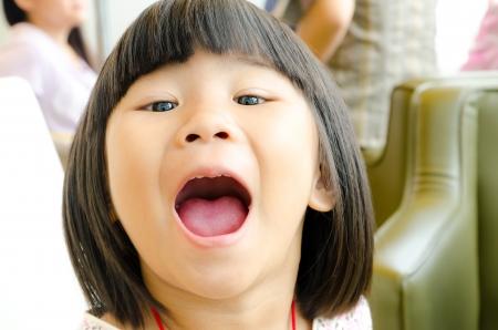 口: 若い女の子が彼女の口を開き、カメラを見て