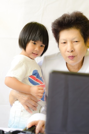 Old woman with girl using laptop computer Stock Photo - 11345924