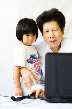 Old woman with girl using laptop computer photo