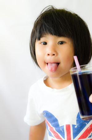 A girl show her tonge with butterfly pea juice photo