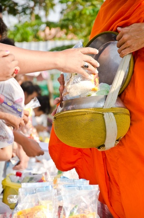 put food offerings in a Buddhist monks alms bowl