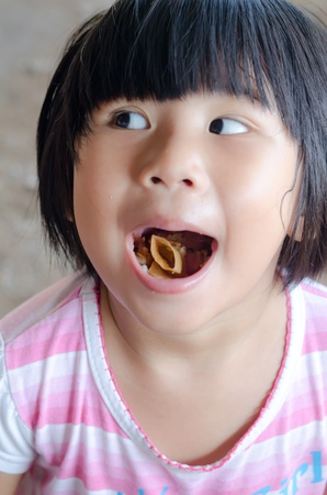 Funny Asian girl open her mouth show food photo