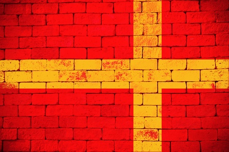 Yellow cross on red brick wall texture photo