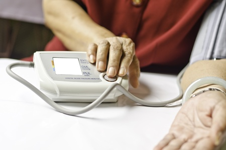 old woman measuring her own blood pressure