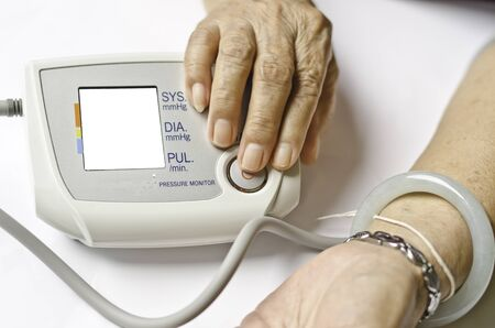 own blood: Old woman measuring her own blood pressure