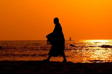 Monk on Hua Hin beach with silhouette photo