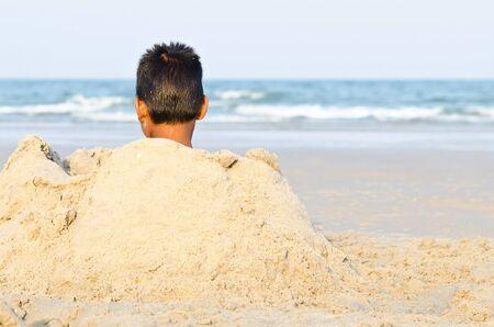 thai boy: Local Thai boy play sand on Hua Hin Beach Stock Photo