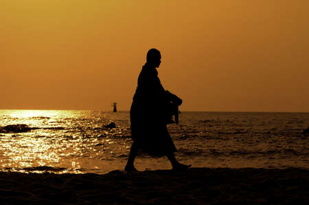 Monk on Hua Hin beach with silhouette Stock Photo - 12924721