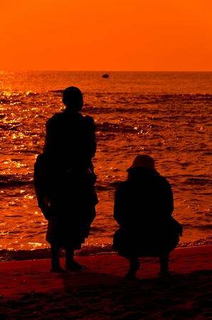 Offering food to  Monk on Hua Hin beach with silhouette Stock Photo - 12983741