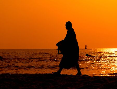 Monk on Hua Hin beach with silhouette Stock Photo - 12983739
