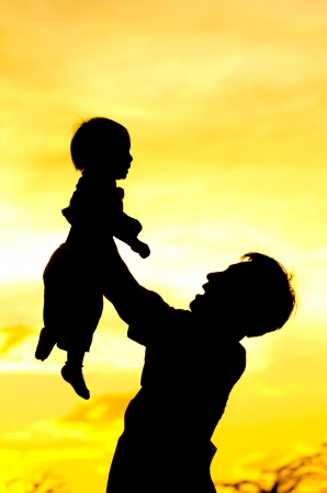 father hold and kiss baby with love.silhouette Stock Photo