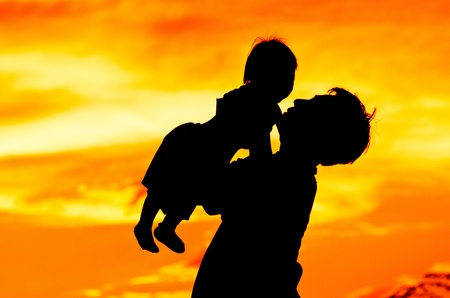 Father hold and kiss baby with love.silhouette photo