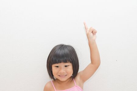 Asian girl point her finger up with white background photo