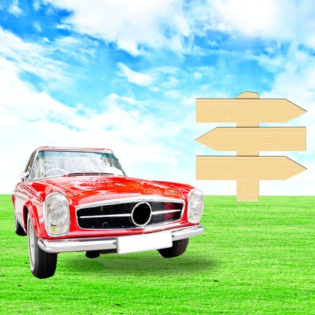 Red vintage car and wooden sign