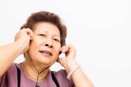 Asian Senior woman listening to music with headphones photo