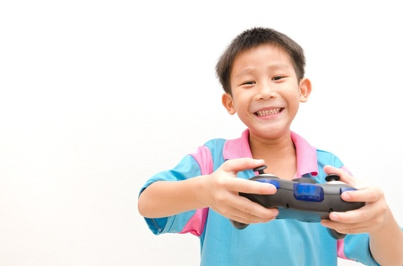 Photo of Asian boy with joystick playing computer game