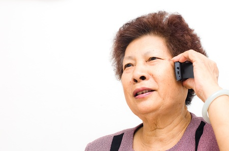 Closeup of a happy senior woman using cellphone over white background photo