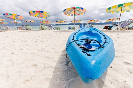 Blue  canoe by a  with beautiful colorful beachbeds and umbella, Phuket Stock Photo - 13425342