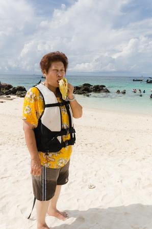 Asian Senior woman enjoy vacation on the beach photo