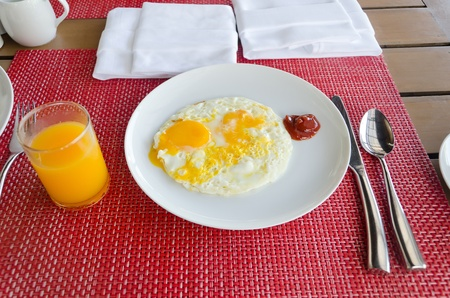 Breakfast with eggs and orange juice on table photo