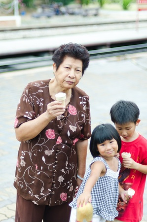 Happy Asian Grandmother with children and icecream, Hua Hin railway station Stock Photo - 13540055