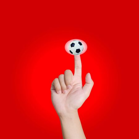 Hand pointing soccer in red background photo
