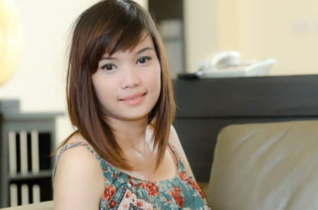 Attrative Asian woman relaxing in living room photo