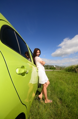Young Asian Woman walking on green field with car photo