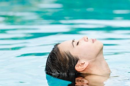 Woman relaxing in swimming-pool