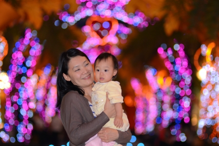 Cute Asian baby girl with mother and night light photo