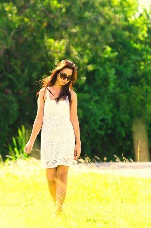 Beautiful girl walks outdoors in the long grass carefree summer emotions Stock Photo