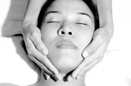 Beautiful young Asian woman receiving facial massage photo